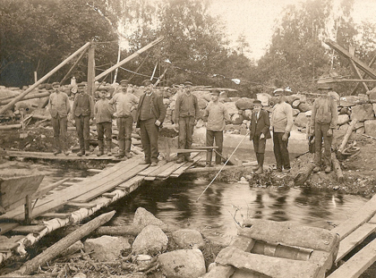 Carl Fritjof Lund (this side of the wheelbarrow) supervises the dam project in early 1909. His son John, wearing a tie and breeches, can be seen fishing.
