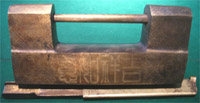 Large box-shaped lock of bronze with etched text; frontsides are shown. Note the coin designs.
